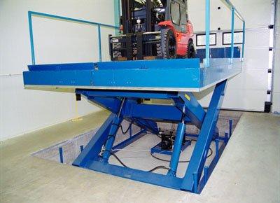 Mesa elevadora para carga y descarga en Interior en foso, con barandillas y topes abatibles.